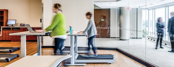 BUSY BODIES At the Mayo Clinic's Dan Abraham Healthy Living Center in Rochester, Minn., employees and other members benefit from on-campus fitness and wellness programs, health screenings, assessments and education. Treadmill desks are used to demonstrate opportunities to incorporate more activity into members' everyday lives. (Photos Courtesy of Dewberry)